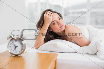 Portrait of a beautiful young woman lying in bed