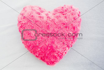 Close up of a pink heart shaped pillow