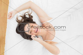 Casual woman using mobile phone in bed