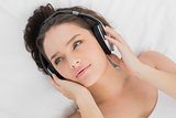 Pretty woman listening to music in bed