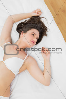 Beautiful young woman lying in bra on bed