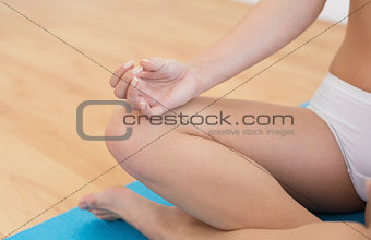 Close up of a slim cropped woman in lotus pose