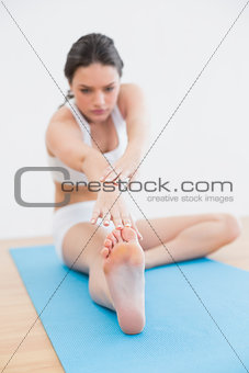 Toned woman doing the hamstring stretch on exercise mat in fitness studio
