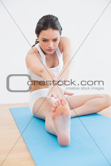 Toned young woman doing the hamstring stretch on exercise mat in fitness studio