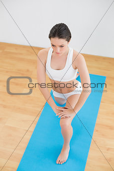 Toned woman stretching leg in fitness studio
