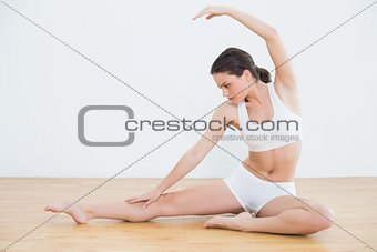 Toned woman stretching hand and leg in fitness studio