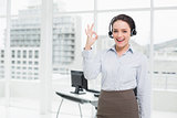 Businesswoman wearing headset while gesturing ok sign in the office