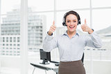 Elegant businesswoman wearing headset while gesturing thumbs up in office