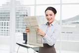 Smiling young businesswoman with newspaper in office
