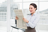 Cheerful businesswoman reading newspaper in office