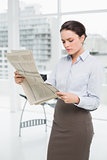 Serious businesswoman reading newspaper in office