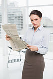 Serious young businesswoman with newspaper in office