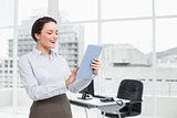 Cheerful businesswoman using table PC in office