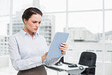 Serious businesswoman using table PC in office