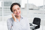 Smiling businesswoman using cellphone in office