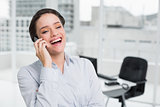 Cheerful elegant businesswoman using cellphone in office