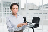 Serious businesswoman holding mobile phone in office