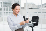 Smiling businesswoman reading text message in office