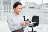 Serious businesswoman reading text message in office