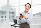 Cheerful businesswoman holding mobile phone in office