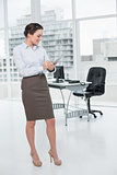 Elegant young businesswoman with clipboard in office