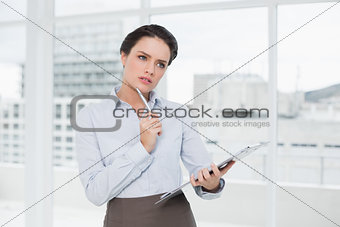 Thoughtful elegant businesswoman with clipboard in office