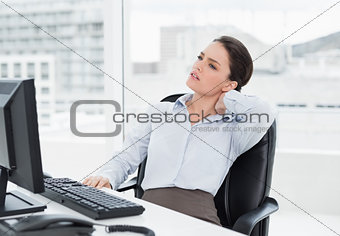 Businesswoman with neck pain sitting at desk