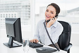 Smiling businesswoman using landline phone and computer in office