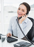 Cheerful elegant businesswoman using landline phone at office desk