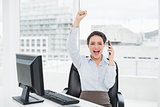 Elegant and happy businesswoman using cellphone in office