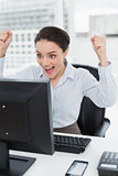 Excited businesswoman looks at the computer screen in office
