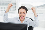 Portrait of an excited businesswoman clenching fists in office