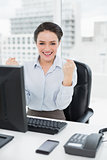 Excited businesswoman clenching fists at office desk