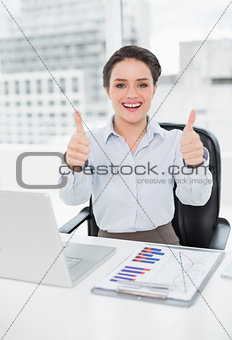 Businesswoman with graphs and laptop gesturing thumbs up in office