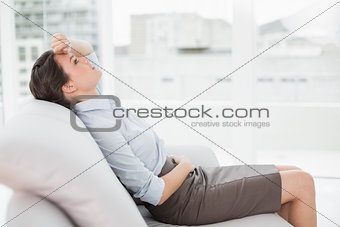 Tired well dressed young woman sitting on sofa