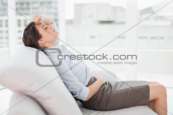 Tired beautiful well dressed woman sitting on sofa at home