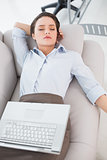 Woman with laptop lying on sofa at home