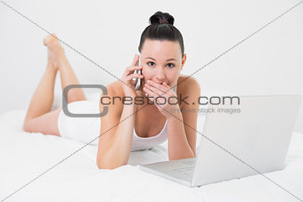 Shocked casual woman using cellphone and laptop in bed