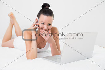 Smiling woman using cellphone and laptop in bed