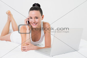 Smiling casual woman using cellphone and laptop in bed