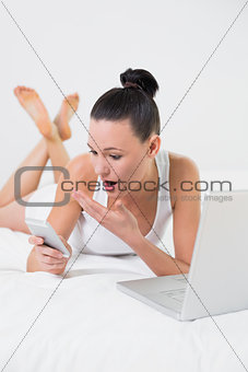 Shocked casual woman with cellphone and laptop