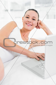Casual smiling woman using laptop in bed