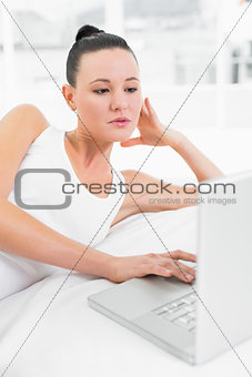 Casual woman using laptop in bed