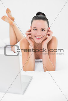Casual smiling woman with laptop in bed