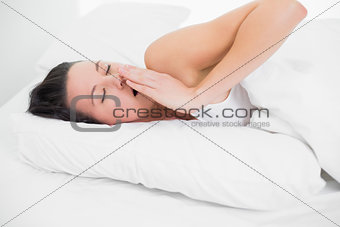 Beautiful woman yawning in bed with eyes closed