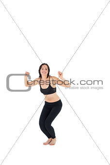 Sporty young woman about to jump over white background