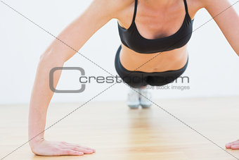 Mid section of a sporty woman doing push ups