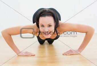 Smiling beautiful woman doing push ups in fitness studio
