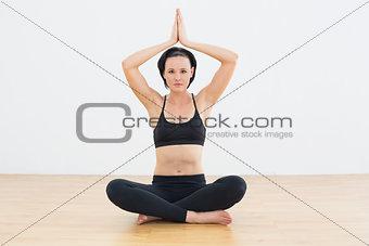 Calm woman in lotus pose meditating at fitness studio