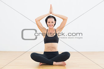 Smiling woman sitting in lotus pose at fitness studio